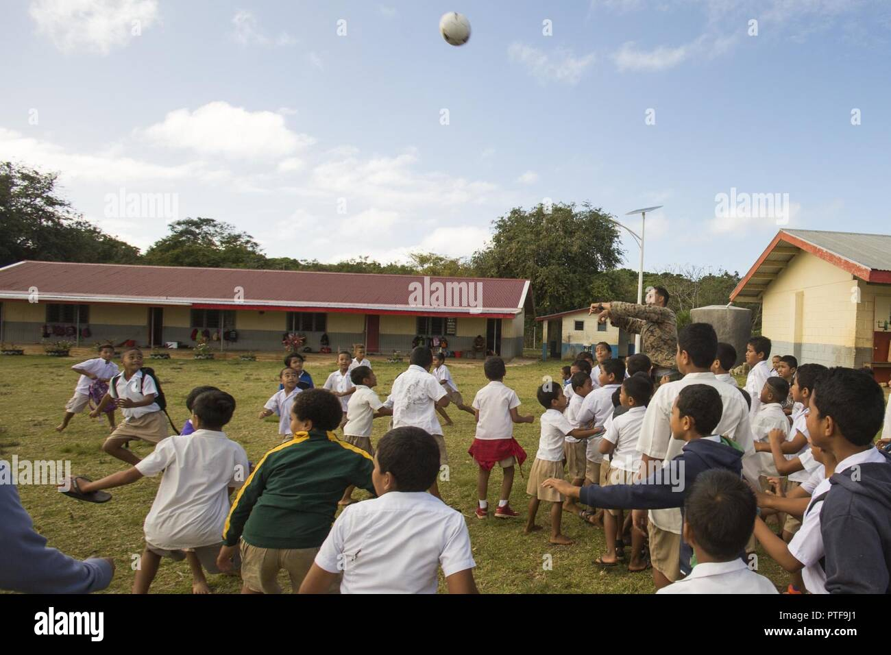 TONGATAPU ISLAND, Tonga — Sgt. Joseph Pritchard throws a ball for children while volunteering at a local elementary school July 20 on Tongatapu Island, Tonga. The volunteers spent part of the day cleaning up the premises, and then participated in a variety of activities with the children during recess. Pritchard is a mortarman with 3rd Battalion, 4th Marine Regiment, currently deployed to Koa Moana 17, and a Port St. Lucy, Florida, native. - Stock Image