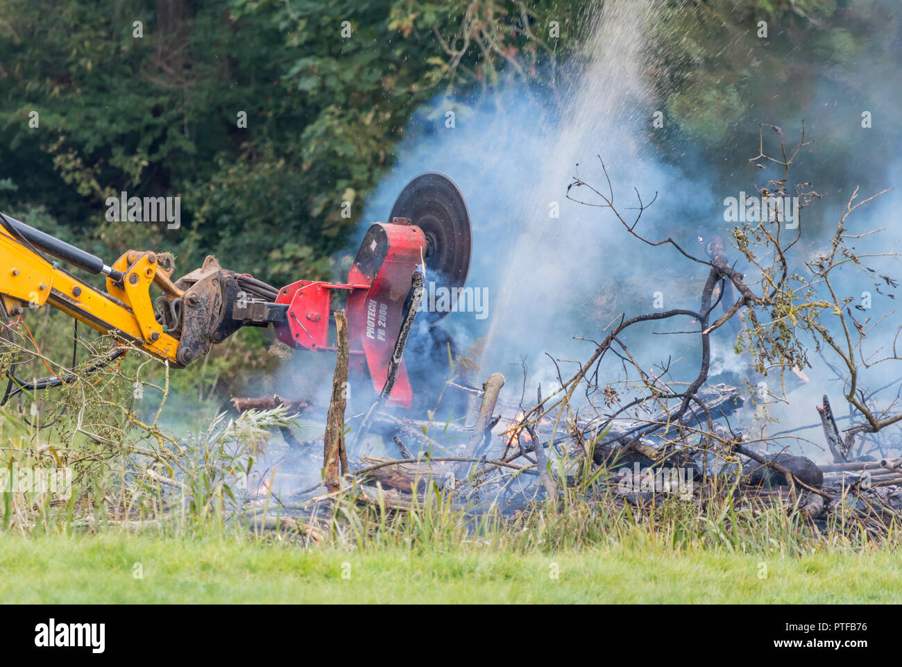 Protech PB2000 (Powerblade 2000) double rotating saw fitted to a tractor, cutting firewood in a bonfire in the countryside, UK. - Stock Image