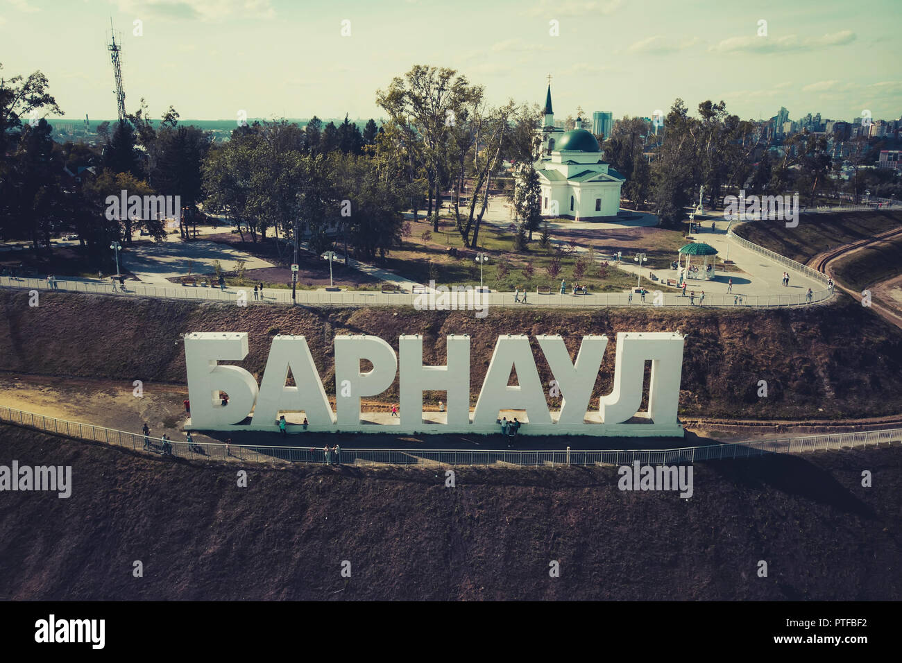 A close up to the hill with the letters spelling out a Russian city's name, a park and a church at the background. Recognized city symbol and architrc - Stock Image