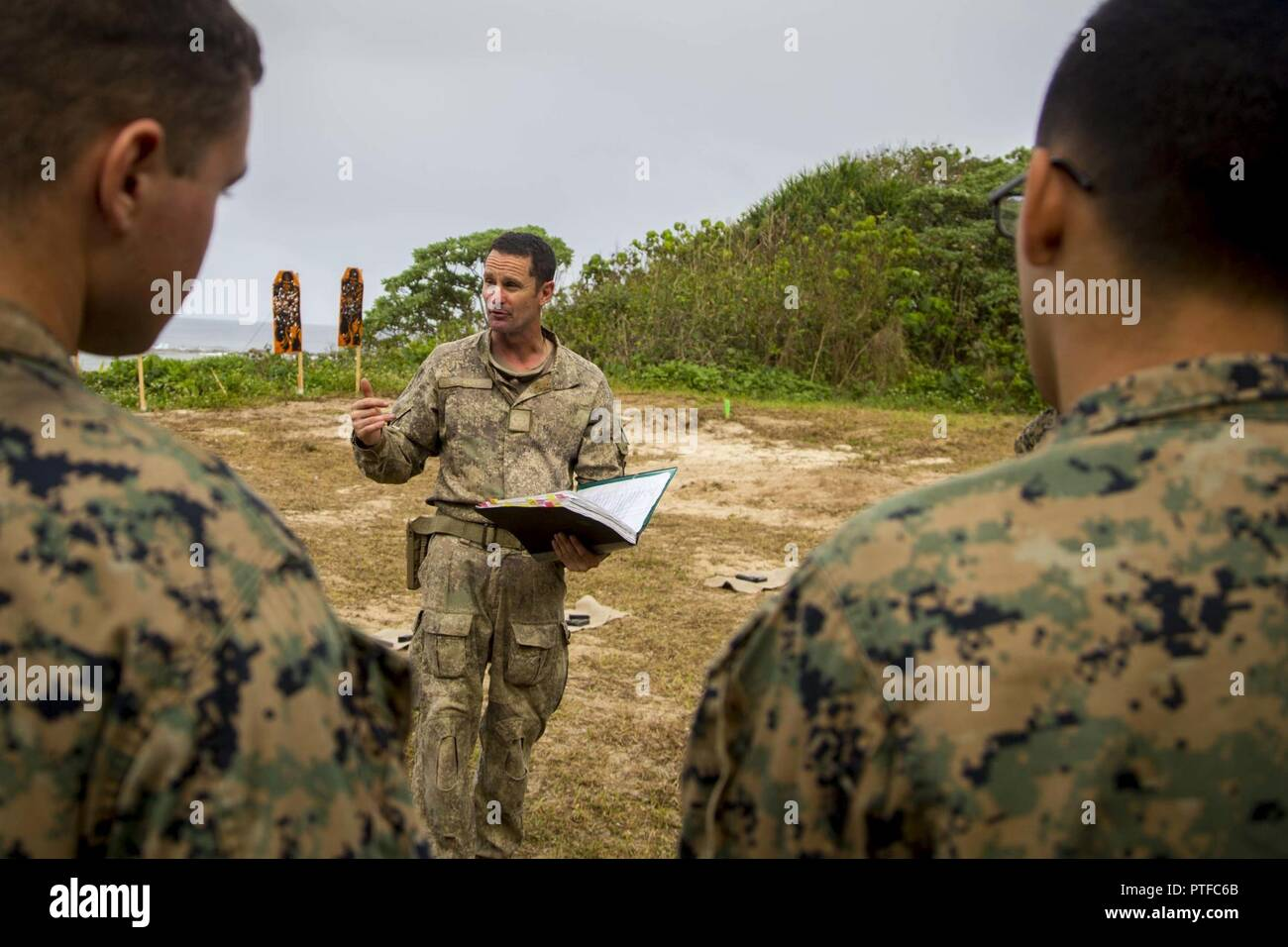 New Zealand Army Sgt. Maj. Paul Buckley, company sergeant major for delta company, explains to U.S. Marines with 3rd Battalion 4th Marines attached to Task Force Koa Moana 17, weapon safety rules prior to participating on a live fire range during Exercise TAFAKULA, on Tongatapu Island, Tonga, July 21, 2017. Exercise TAFAKULA is designed to strengthen the military-to-military, and community relations between Tonga's His Majesty's Armed Forces, French Army of New Caledonia, New Zealand Defense Force, and the United States Armed Forces. Stock Photo