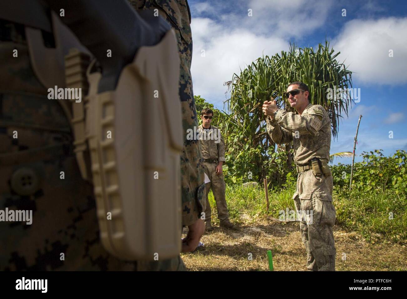 New Zealand Army Sgt. Maj. Paul Buckley, company sergeant major for delta company, shows U.S. Marines with 3rd Battalion 4th Marines attached to Task Force Koa Moana 17, how to properly hold the glock 17 during Exercise TAFAKULA, on Tongatapu Island, Tonga, July 21, 2017. Exercise TAFAKULA is designed to strengthen the military-to-military, and community relations between Tonga's His Majesty's Armed Forces, French Army of New Caledonia, New Zealand Defense Force, and the United States Armed Forces. Stock Photo