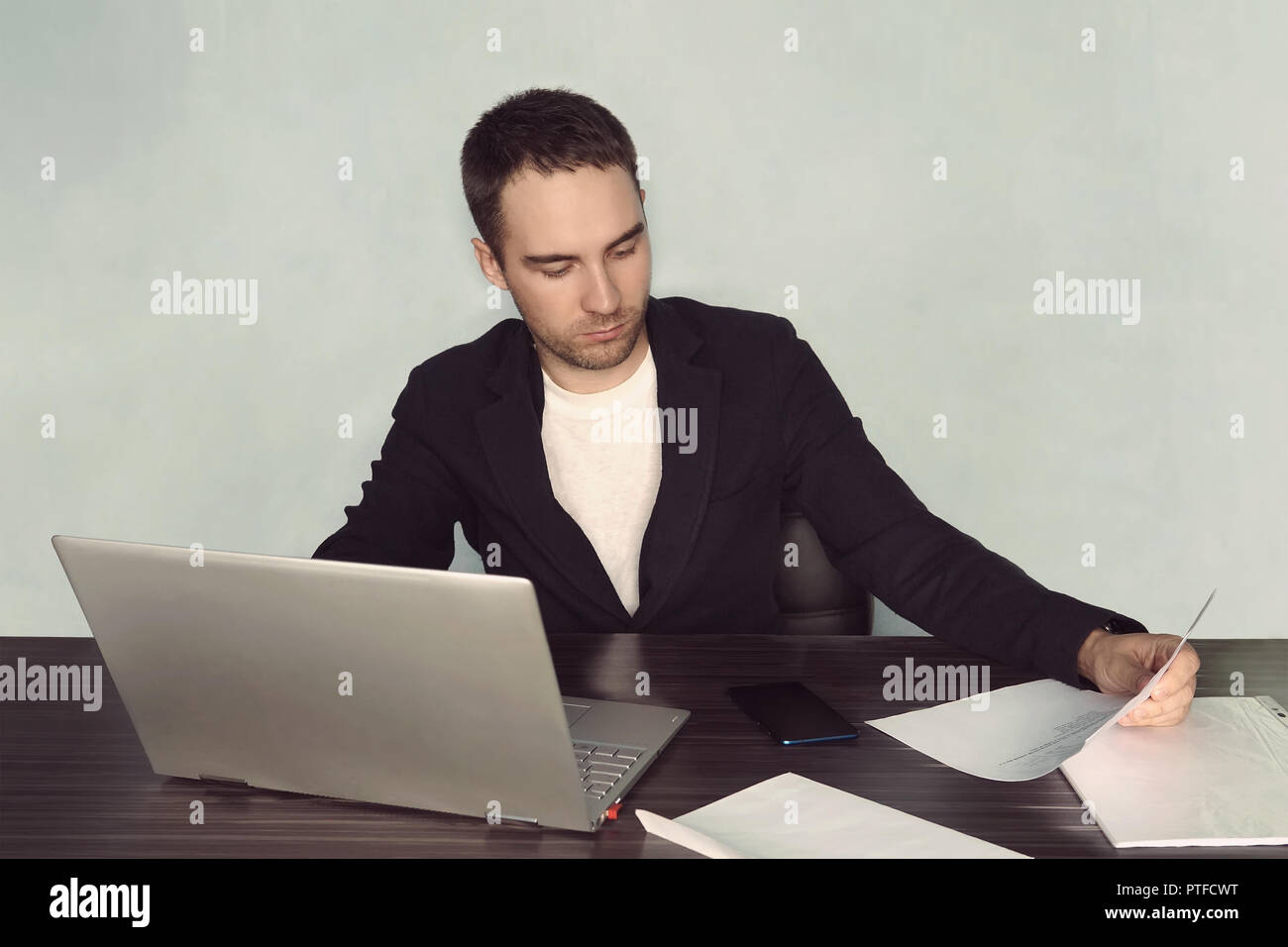 Image concentrated unshaved businessman 30s in white t-shirt holding and looking at clipboard with paper documents during work in office. tired worker - Stock Image