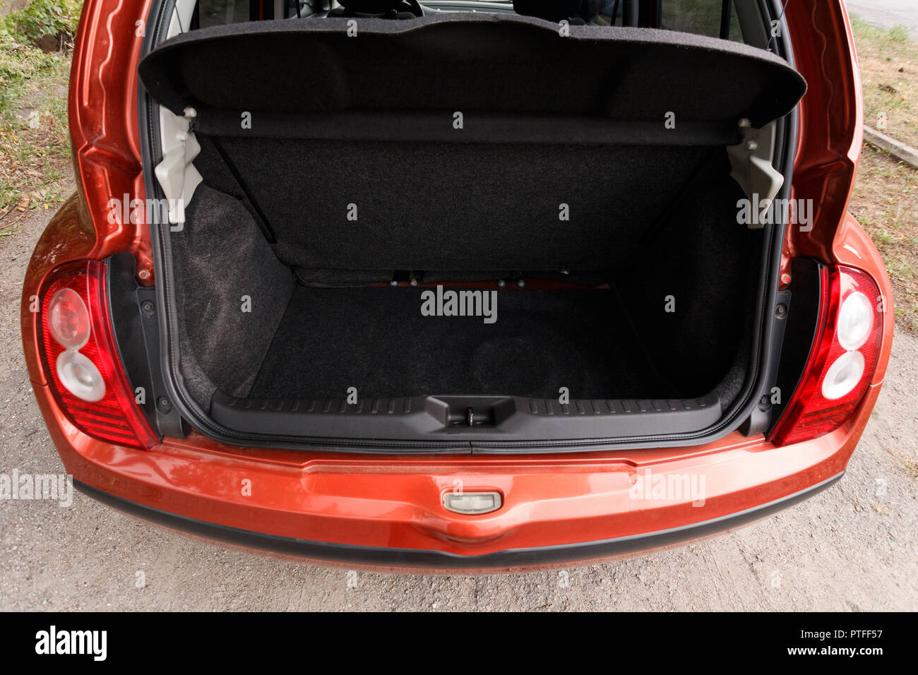 Car with open clean empty trunk of orange hatchback - Stock Image