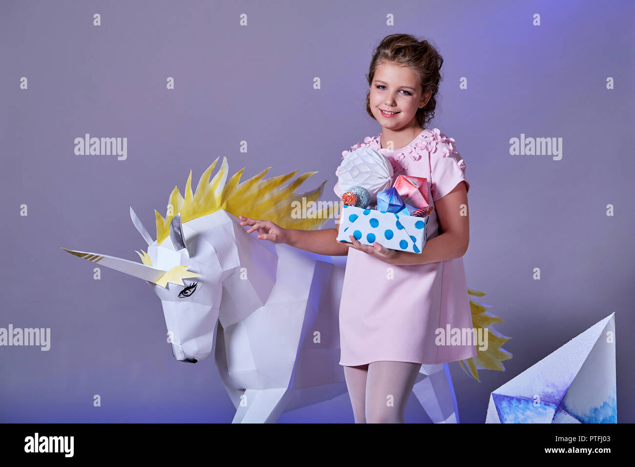 a52e32383c2b6 Beautiful caucasian teen girl in elegant pink dress holding box of origami.  Fashion kid eve Christmas,new year,holiday. Child portrait make-up.