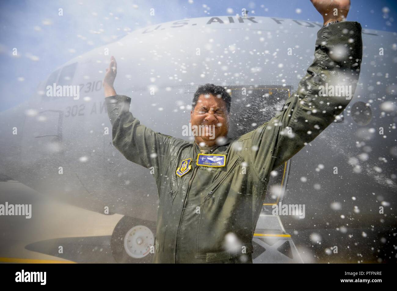 Air Force Reserve Lt. Col. Tora Gore, a C-130 flight test navigator with the 339th Flight Test Squadron, receives showers of water and champaign after flying his last mission before retirement July 20, 2017, at Robins Air Force Base, Ga. Gore completed 10 years of Air Force active-duty service before joining the Alaska Air National Guard in 2004 and the Air Force Reserve in 2008. - Stock Image