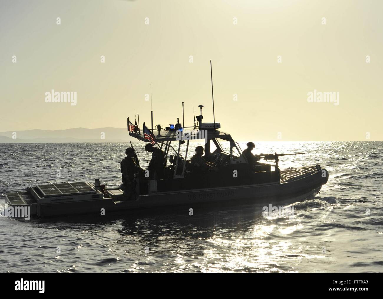 Coast Guardsmen from Port Security Unit 305 aboard a 32-foot Transportable Port Security Boat enforce a security zone off the coast of Naval Station Guantanamo Bay, Cuba, Wednesday, July 19, 2017. PSU 305 is deployed to Naval Station Guantanamo Bay to provide mission support for the Department of Defense. U.S. Coast Guard Stock Photo