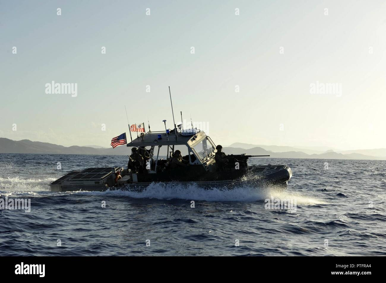 Coast Guardsmen from Port Security Unit 305 aboard a 32-foot Transportable Port Security Boat patrol the waters off the coast of Guantanamo Bay, Cuba, Wednesday, July 19, 2017. PSUs are reserve-staffed units who train in preparation for deployments capable of conducting joint operations worldwide in support of the Department of Defense. U.S. Coast Guard Stock Photo