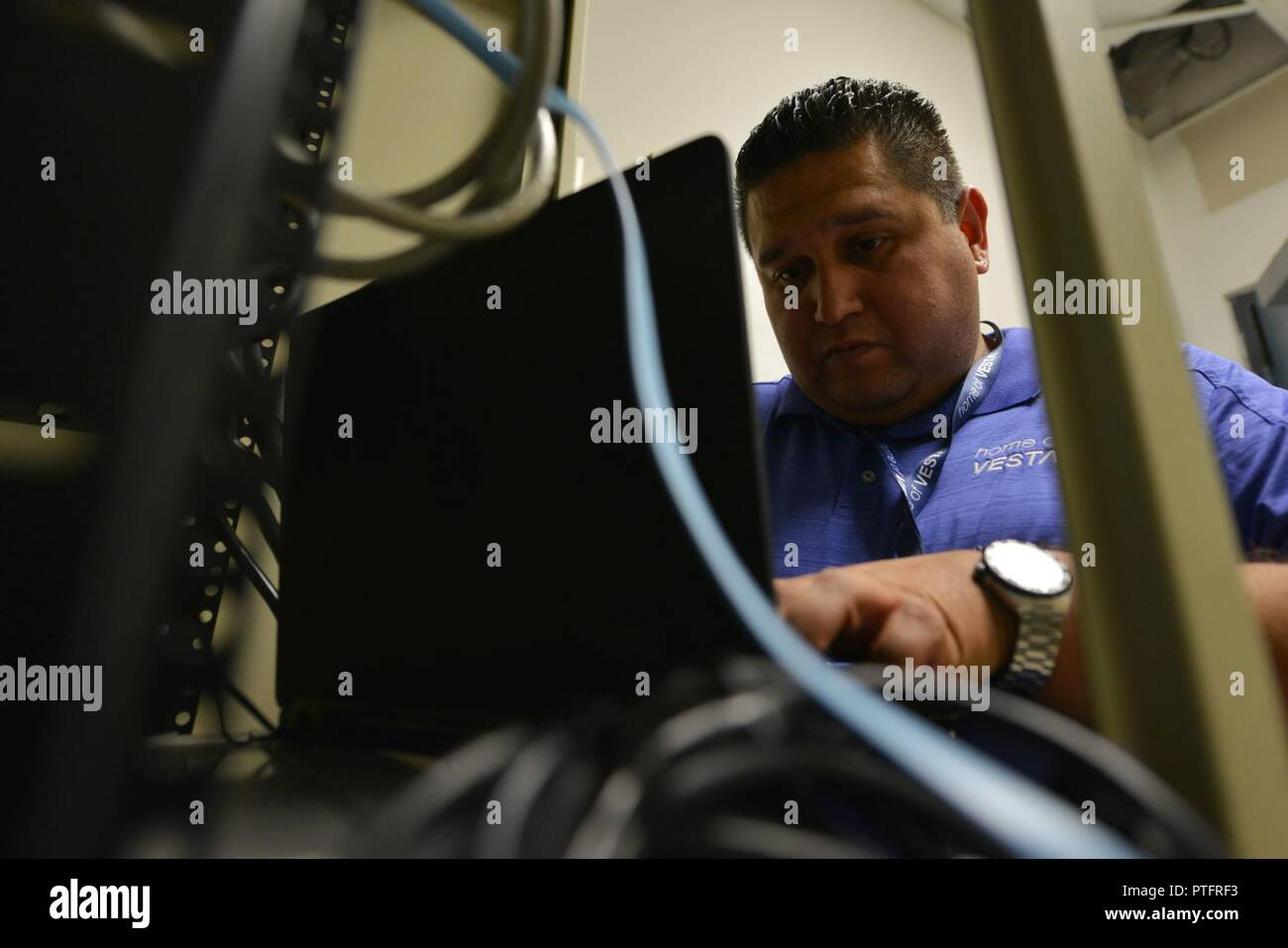 Jimmie De Armes, field engineer, configures a route from the emergency consoles to the communications server to allow the two systems to communicate at Shaw Air Force Base, S.C., July 12, 2017. De Armes configured the route for the Enhanced 911 system which received software and hardware updates, increasing speed and security. Stock Photo