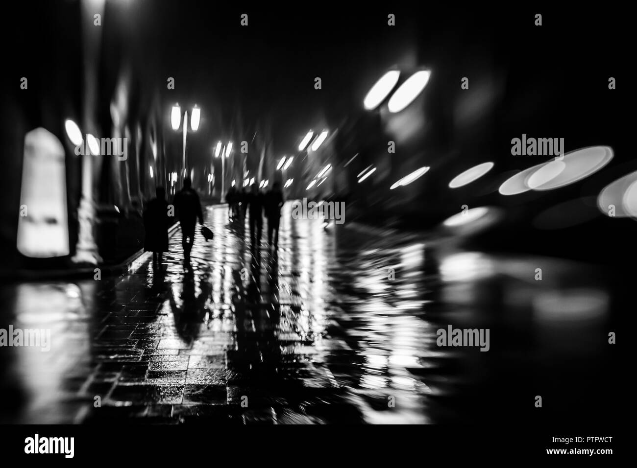 Silhouettes of people like zombie walking at night in the rainy in the light of street lamps,soft blurred focus. - Stock Image