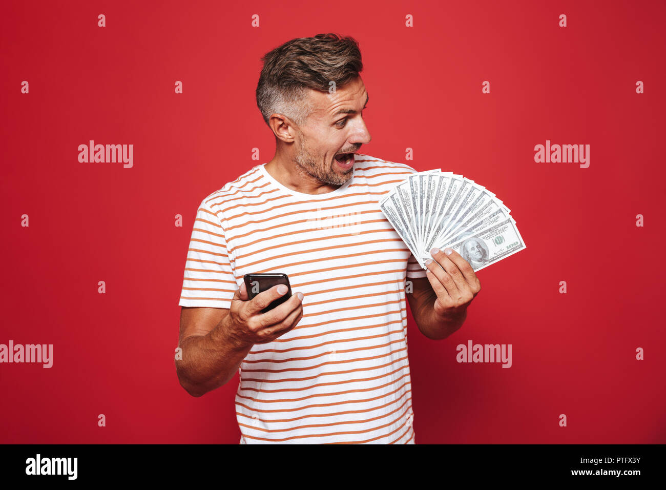 Portrait of a happy man standing over red background, using mobile phone, showing money banknotes Stock Photo
