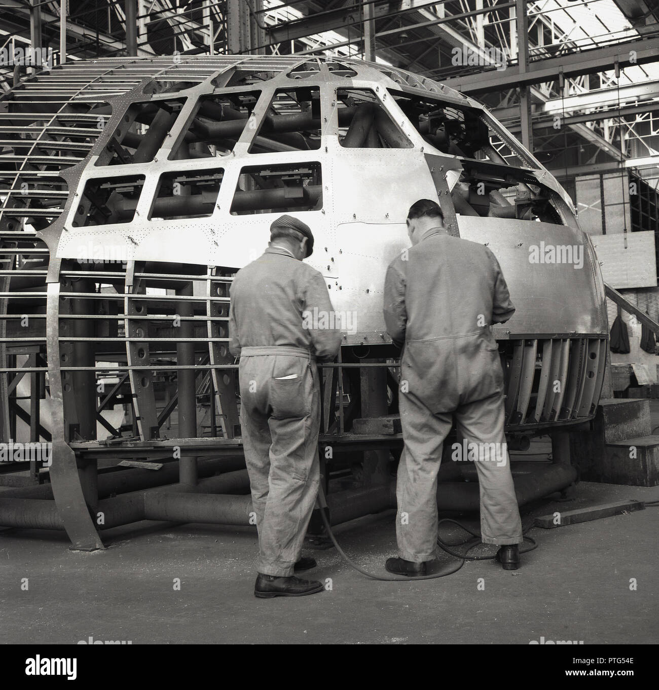 1950s, historical, aviation, two male mechanics or engineers in overalls working on the exterior of an aircraft cockpit inside an aerospace factory or hanger, England, UK. - Stock Image