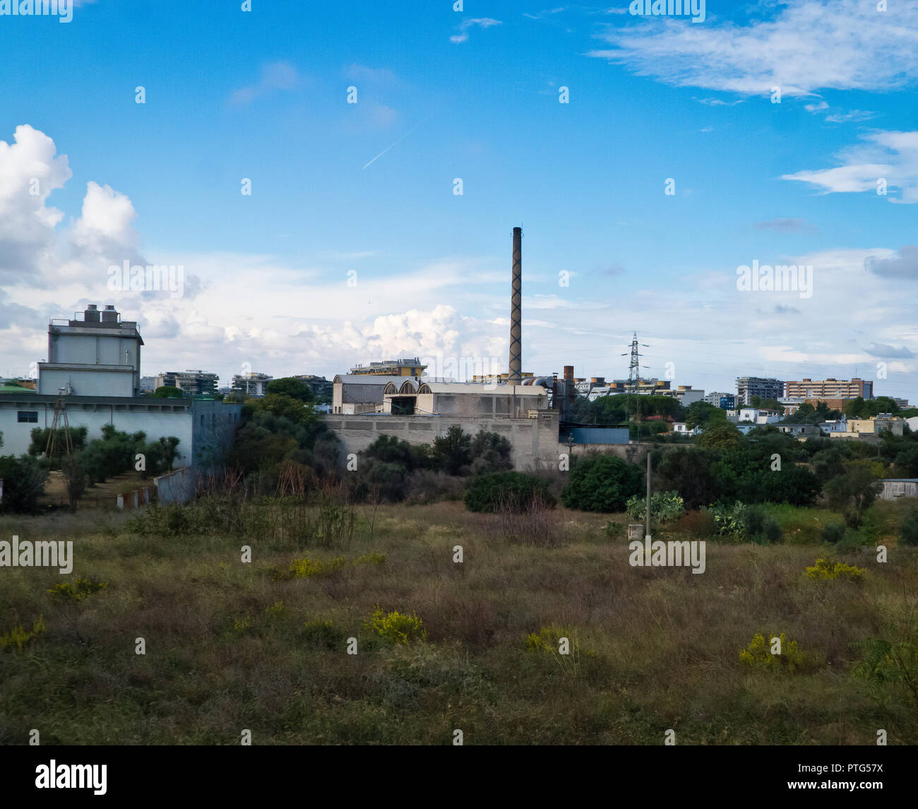 Periphery of Bari city landscape,with chimnery of abandoned industrial build. - Stock Image