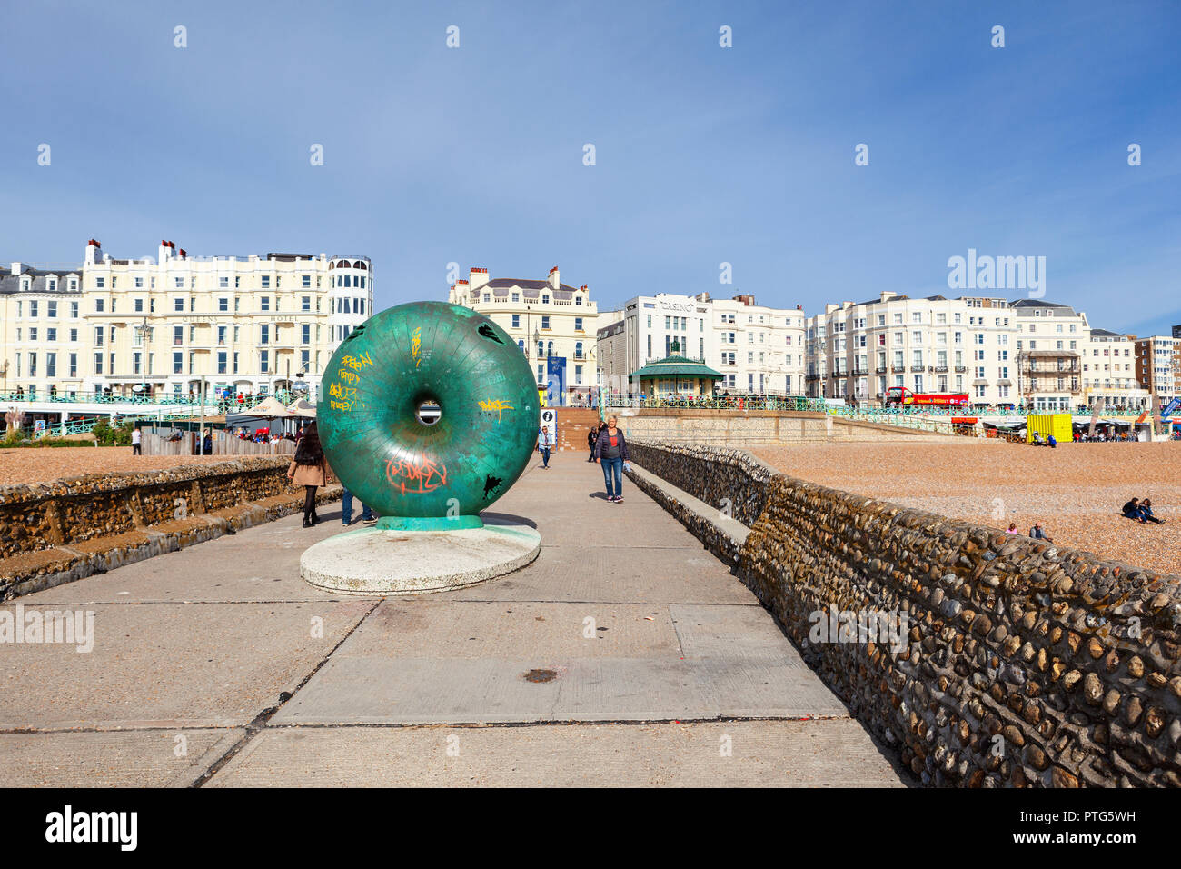 Brighton, England, October 07, 2018. View of Brighton beach behing the public artwork 'Afloat', circular donut shaped globe cast in bronze created by  - Stock Image