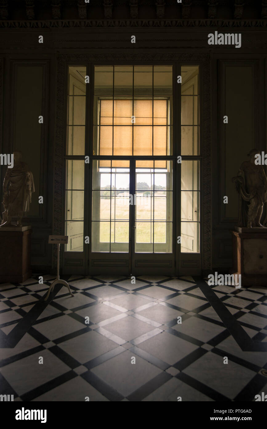 Glass door entrance reflected in marble at Standen House, Sussex Stock Photo