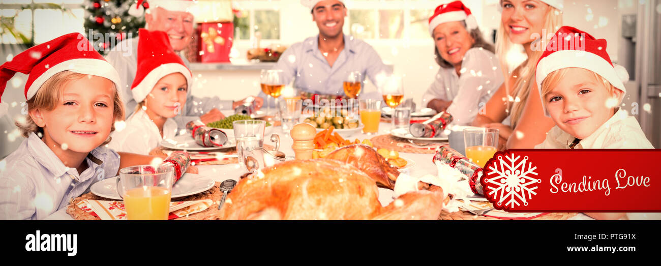 802d24210bcdd Composite image of happy family wearing santa hats around the dinner table