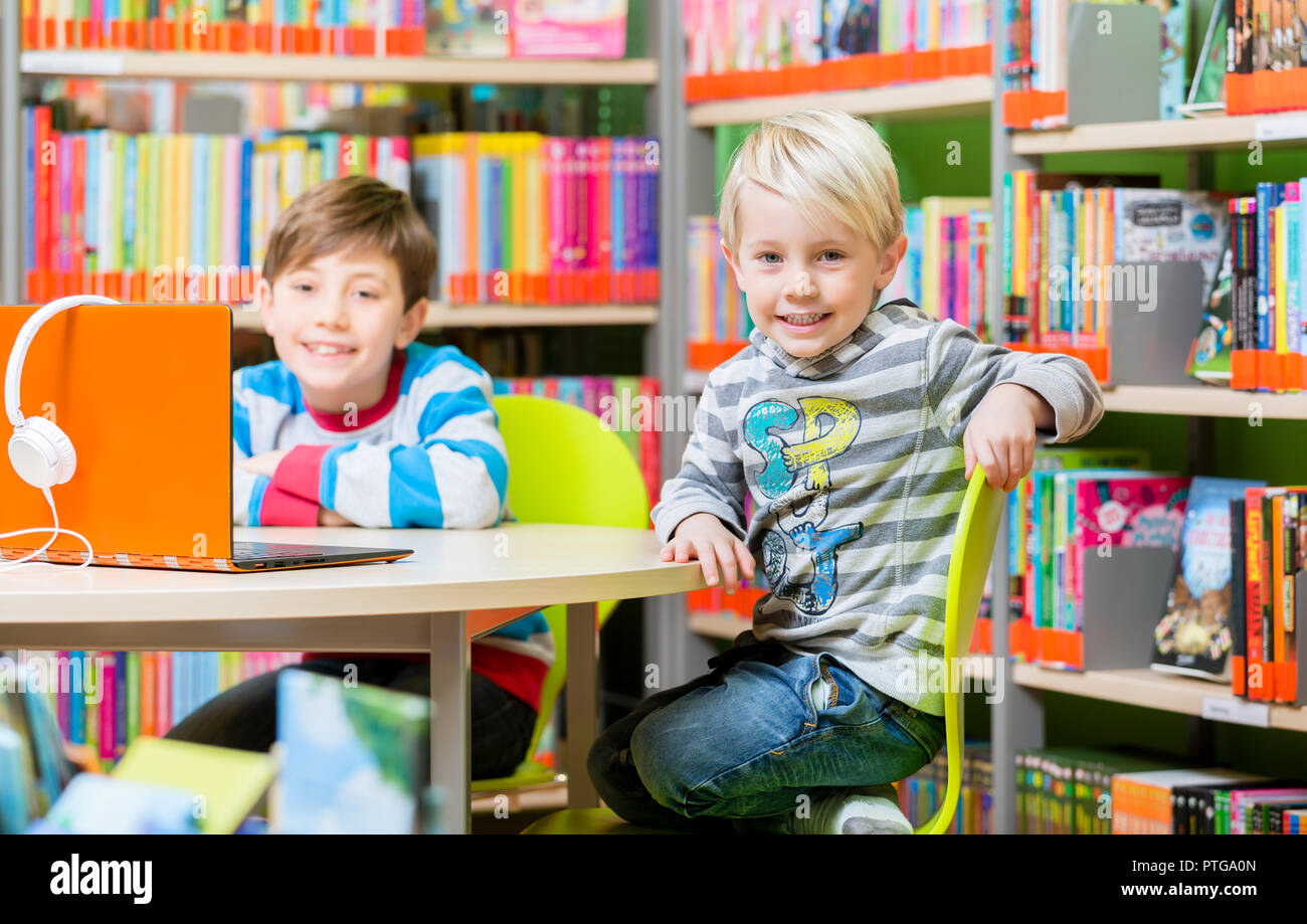 Brothers in the library reading books and listening to audio having fun