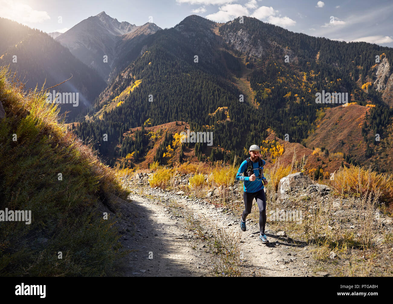 Runner athlete with beard running on the trail in the mountains - Stock Image