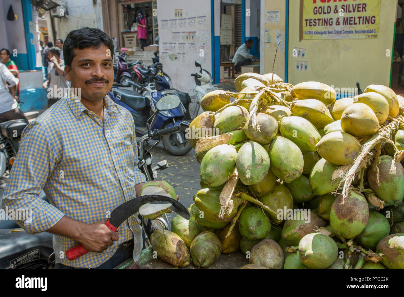 Coconut seller at an Indian Market. Photographed in Ahmedabad, Gujarat, India - Stock Image