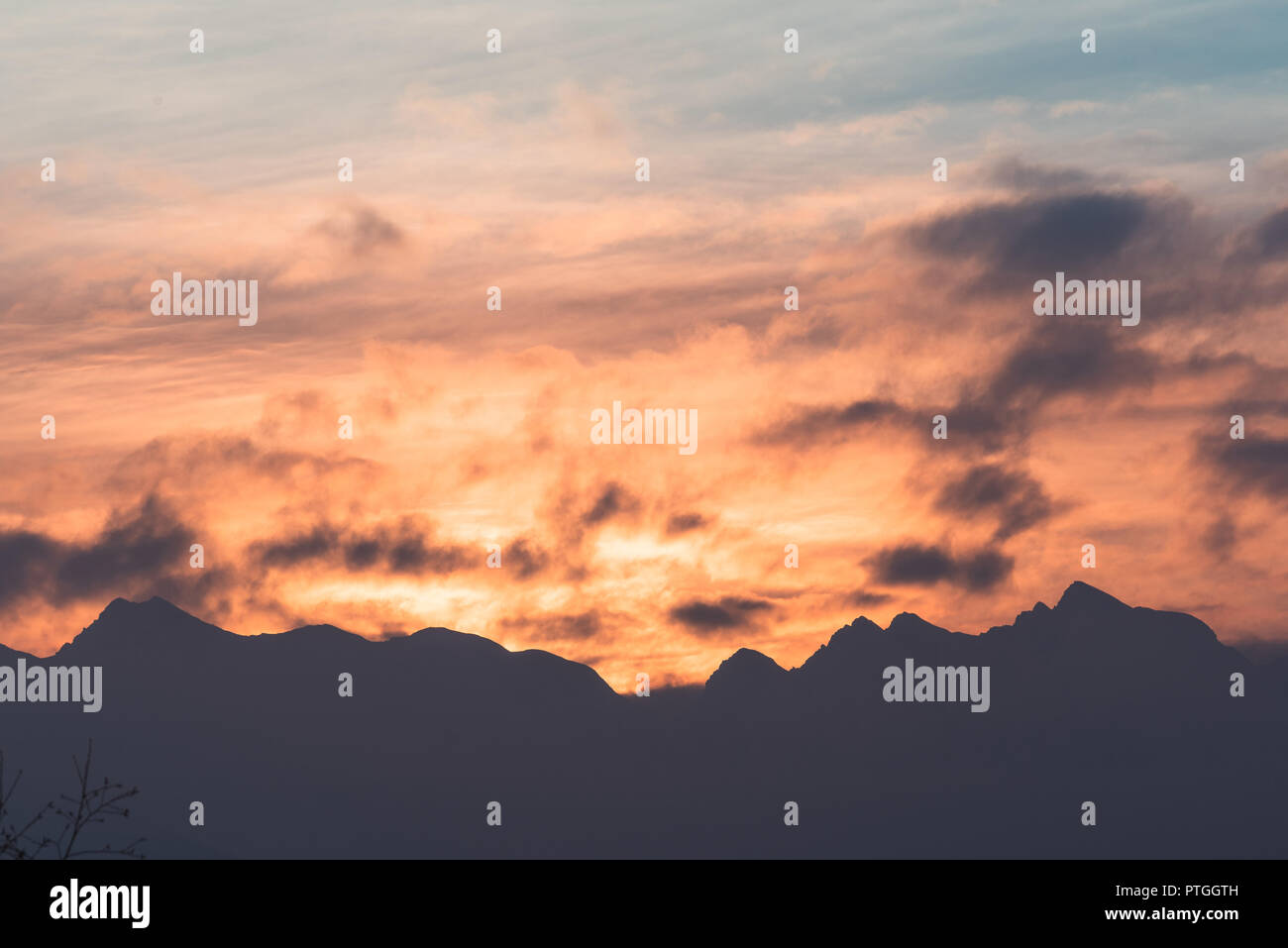 Orange Sunset With Distant Mountain Peaks With Clouds Blue
