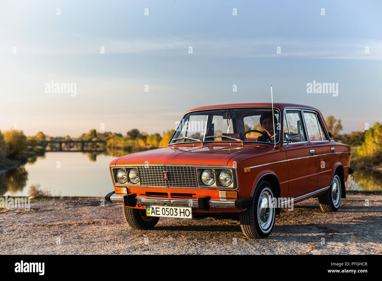 PERESHCHEPINO, UKRAINE - OCTOBER 12, 2014: Zhiguli VAZ 2106 original orange, released in the USSR in 70's. Car parked on the side of the road in the m Stock Photo