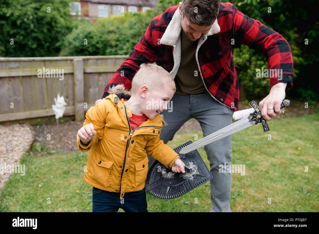 Little boy and his father playing in the front garden on the grass. They are playing with a toy sword and sheild. They are laughing and having fun tog - Stock Image