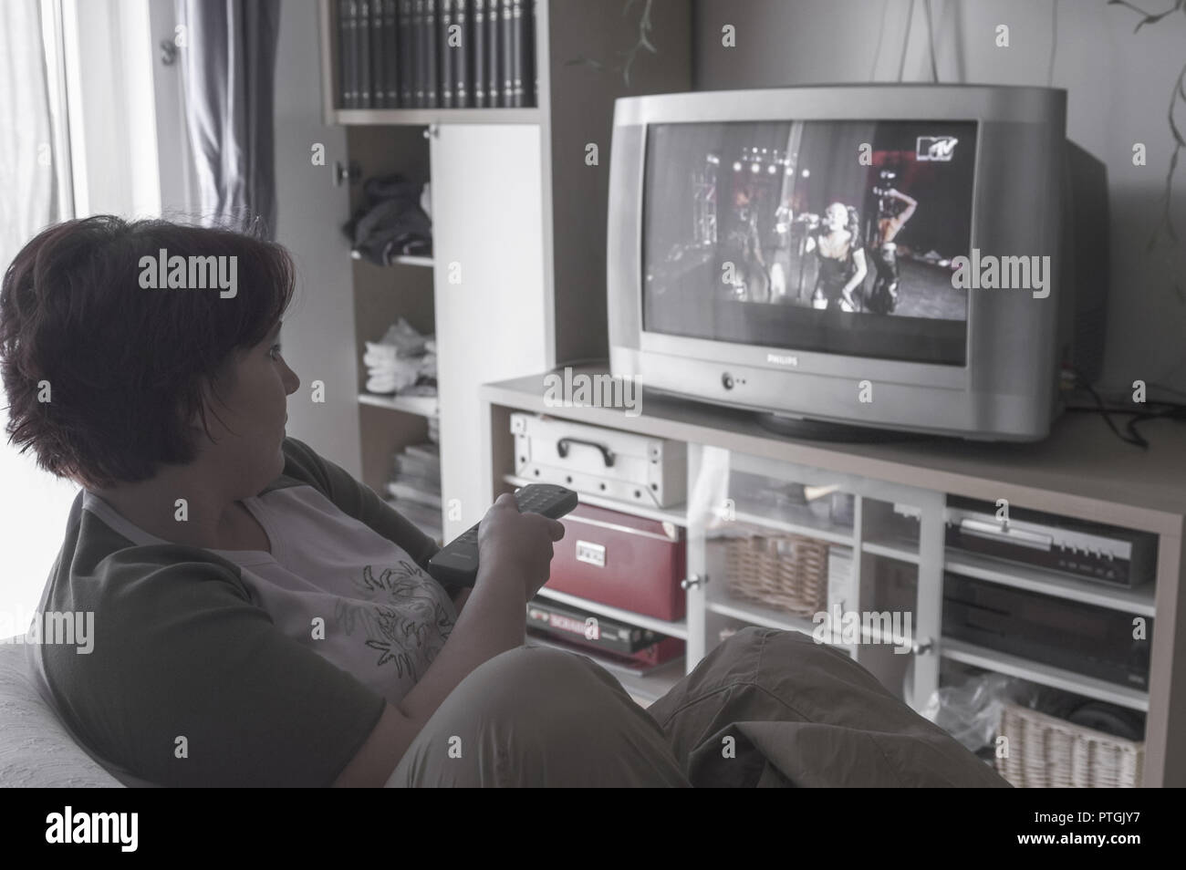 Young woman in front of TV screen, watching TV (model