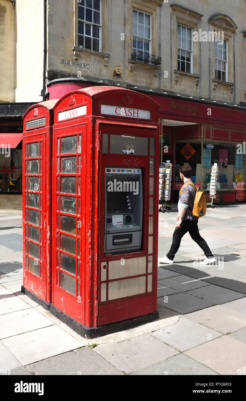 A red classic telephone box which has been converted to a cash ATM in Bath UK. 2018. Stock Photo