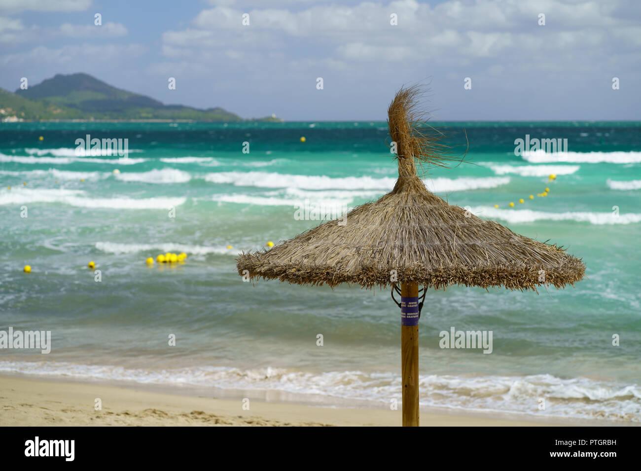 Straw Umbrella on the Beach, Playa de Muro, Alcudia, Mallorca, Spain - Stock Image