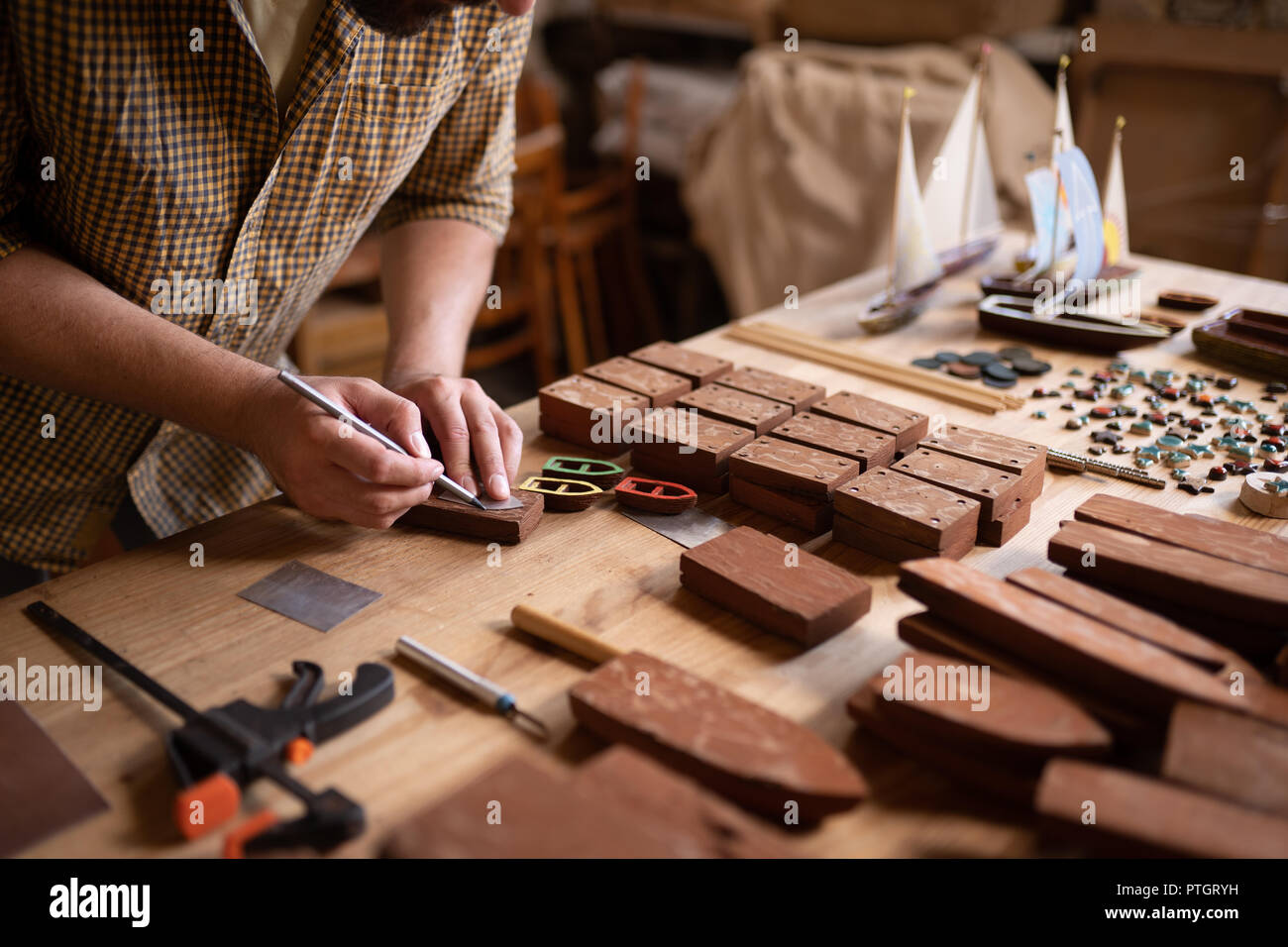 A close-up view of a joiner using a pencil to cope a shape of boat on wood. - Stock Image