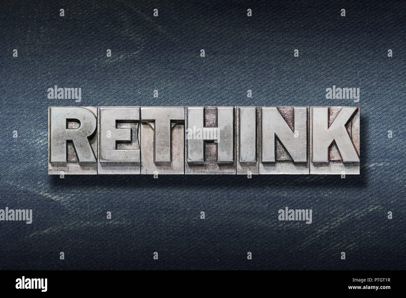 rethink word made from metallic letterpress on dark jeans background - Stock Image