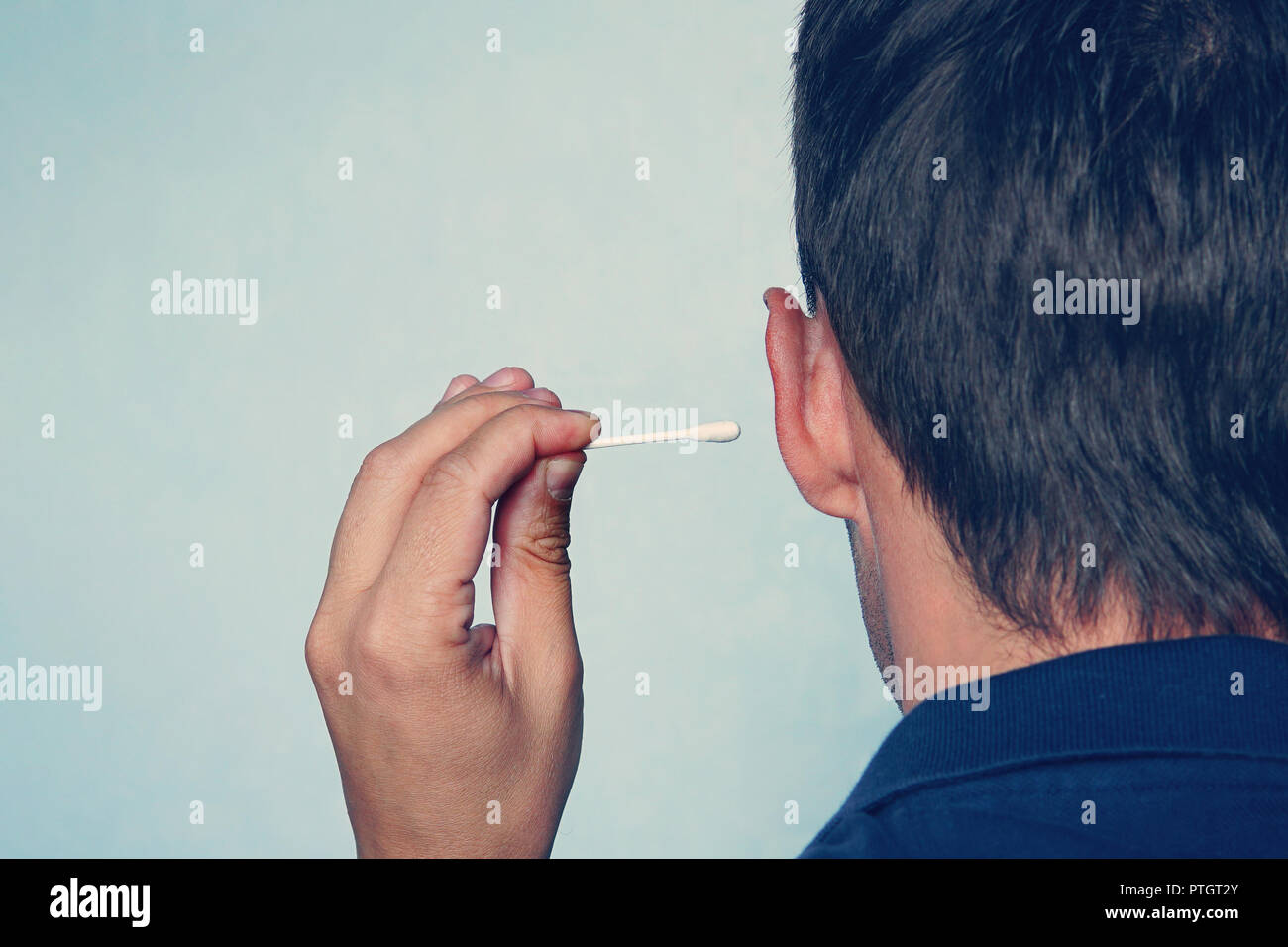 Happy man cleans his ear with a cotton swab close-up on blue background. - Stock Image