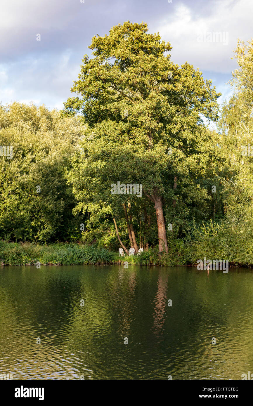 A group of metal white garden table and chairs stand on the bank of the River Thames at Iffley, Oxford, Oxfordshire, UK - Stock Image