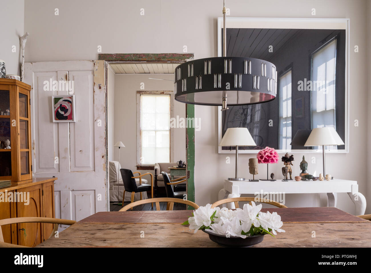 c18 New England drop leaf table and Wishbone chairs by Hans J Wegner. Console by Daryl Lauster with print by Richard Serra. - Stock Image