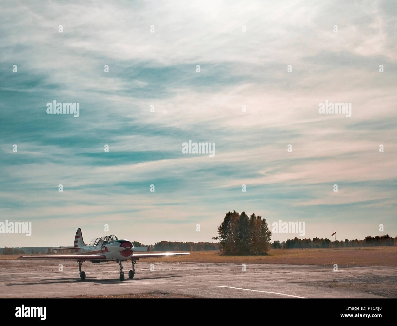 View of airplane on grassy airfield close up; classic plane taxiing to takeoff on runway; training aerobatic flight of oldschool aircraft; leisure act - Stock Image