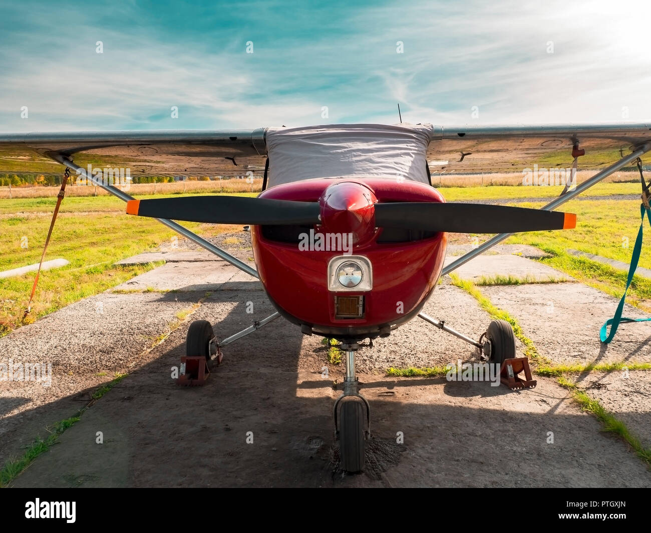 View of classic airplane on the grassy airfield; aircraft after the flight with cases on propellers and other elements; front view of small sport silv - Stock Image