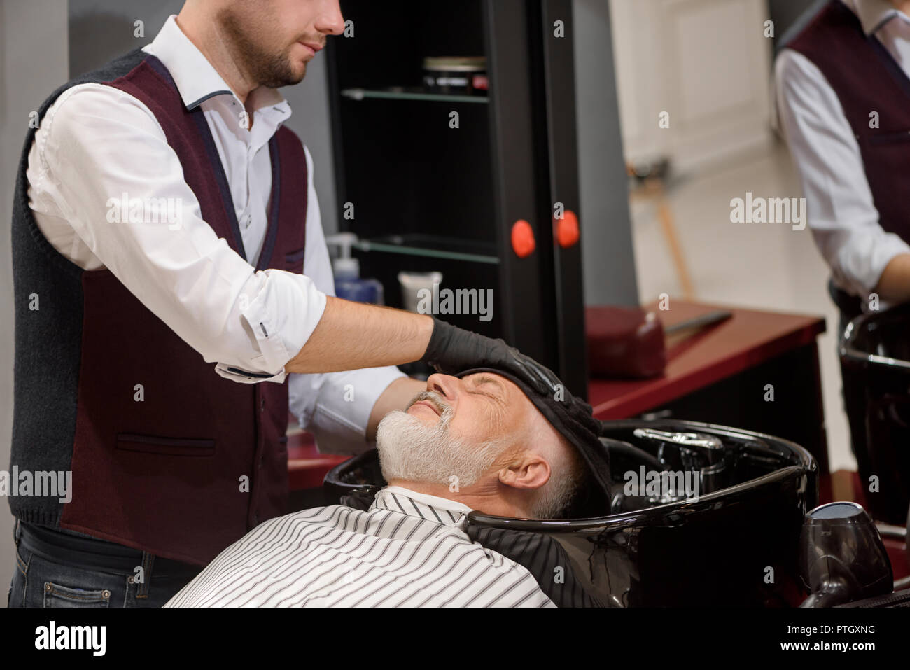 Unrecognizable barber wiping head of client with towel in black wash basin. Male hairdresser styling hair of old client with grey beard. Hairstylist working in barbershop. - Stock Image