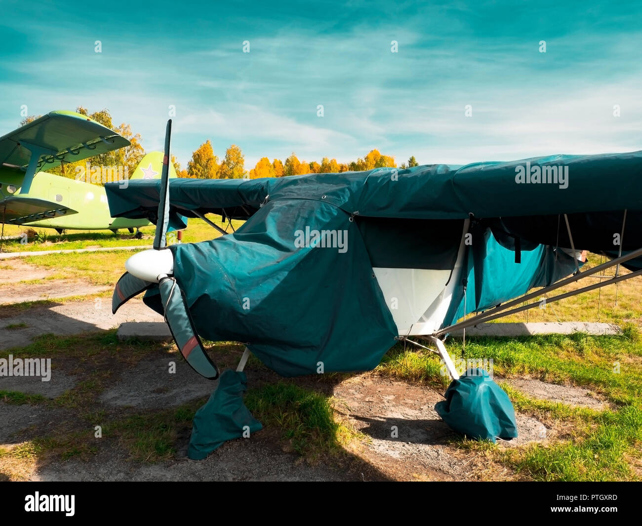 View of classic airplane on the grassy airfield; aircraft after the flight with cases on propellers and other elements; leisure activity and entertain - Stock Image