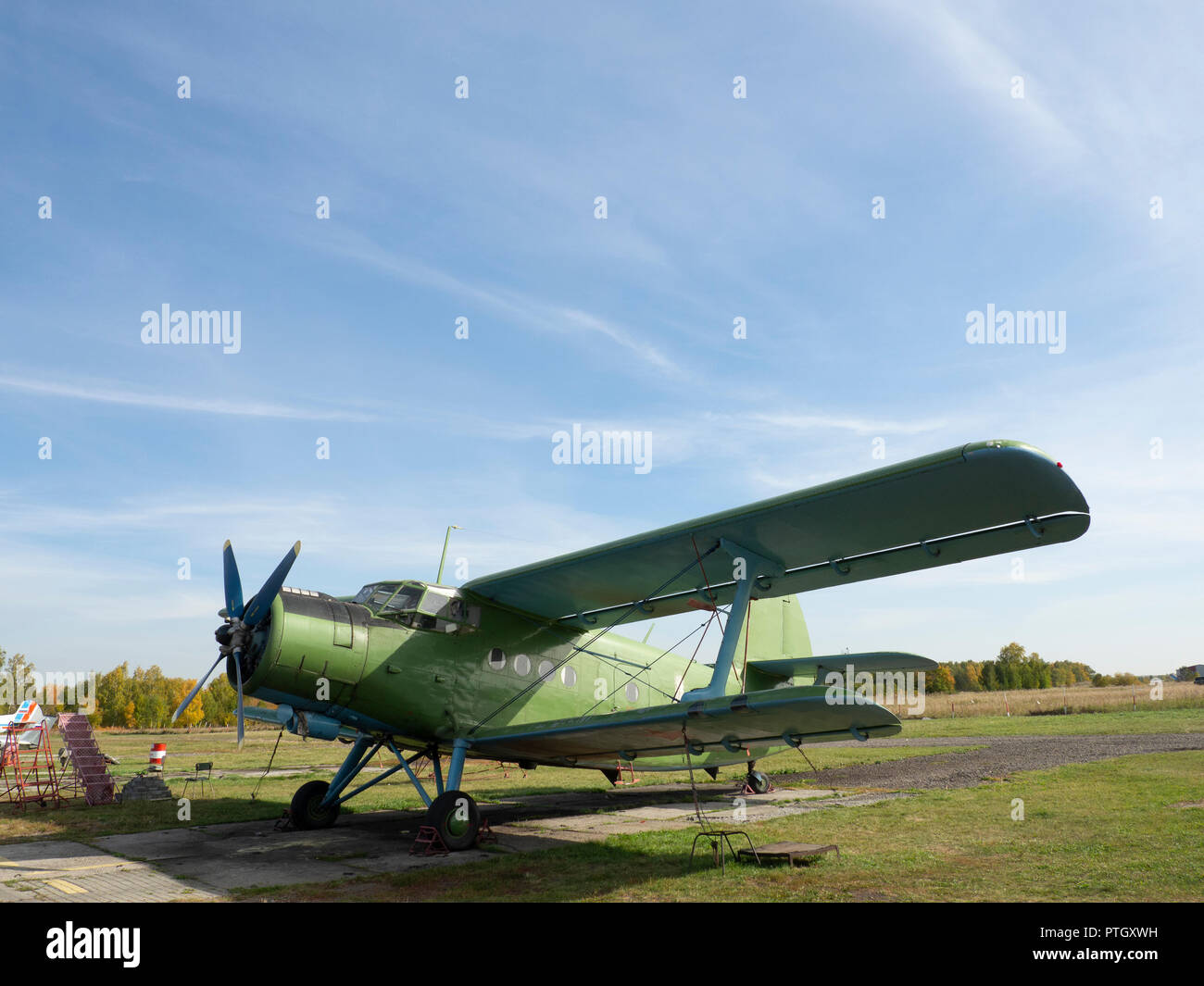 View of classic airplane on the grassy airfield; aircraft after the flight with cases on propellers and other elements; green military aircraft on the - Stock Image
