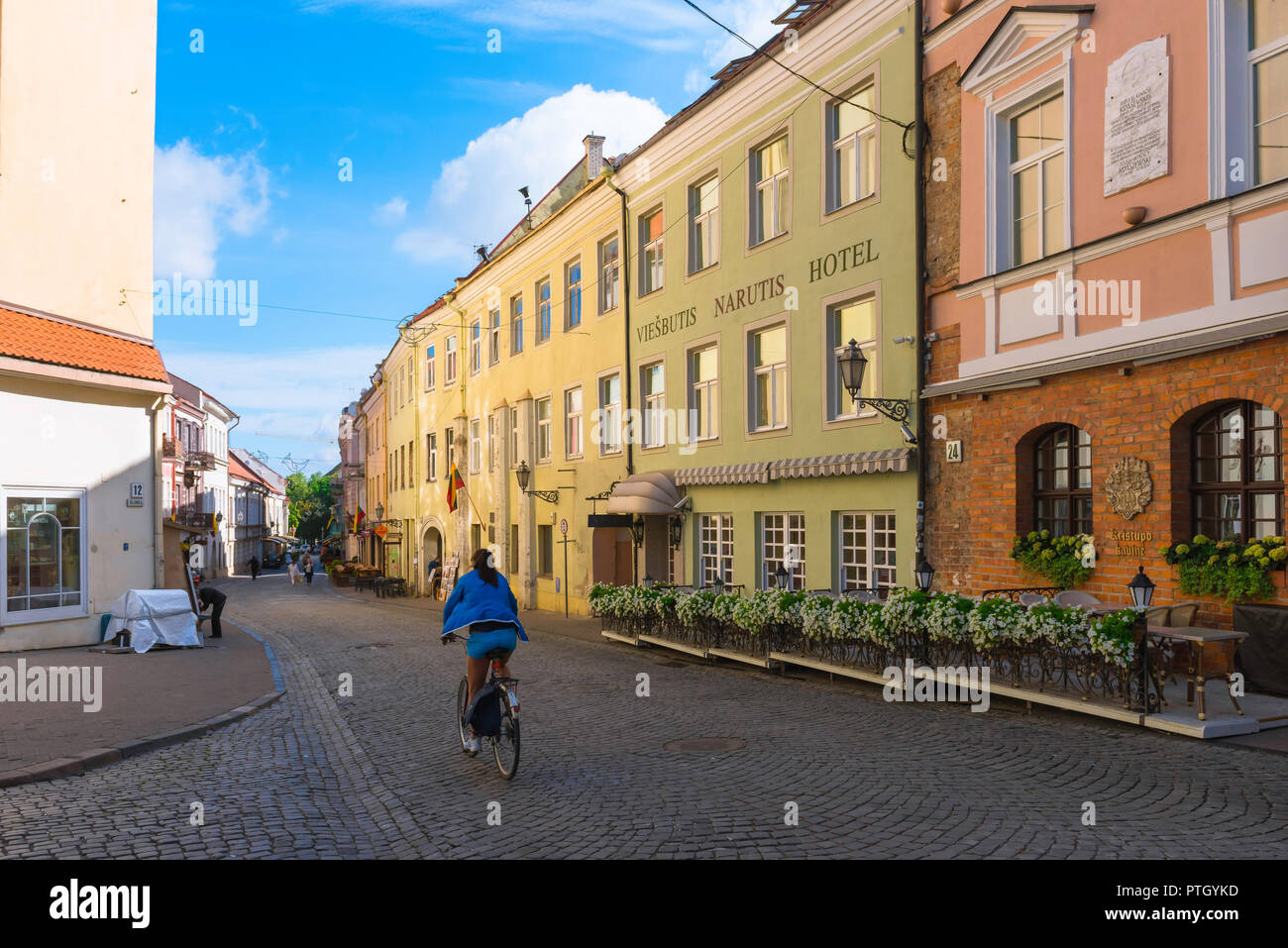 Vilnius old town, view on a summer morning of a young woman cycling along Pilies Gatve - the main thoroughfare in Vilnius Old Town, Lithuania. Stock Photo