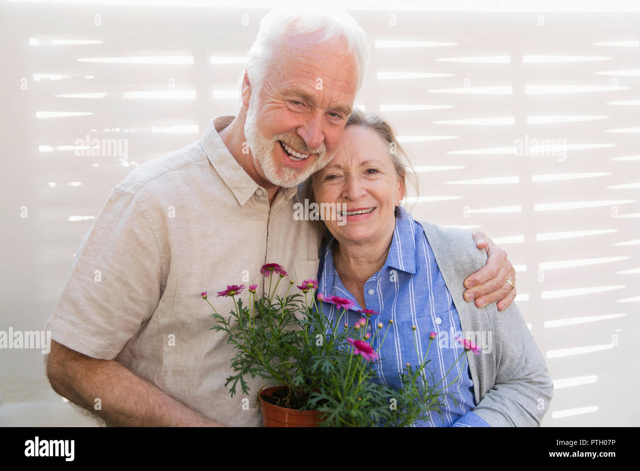 Portrait happy active senior couple with flowerpots - Stock Image