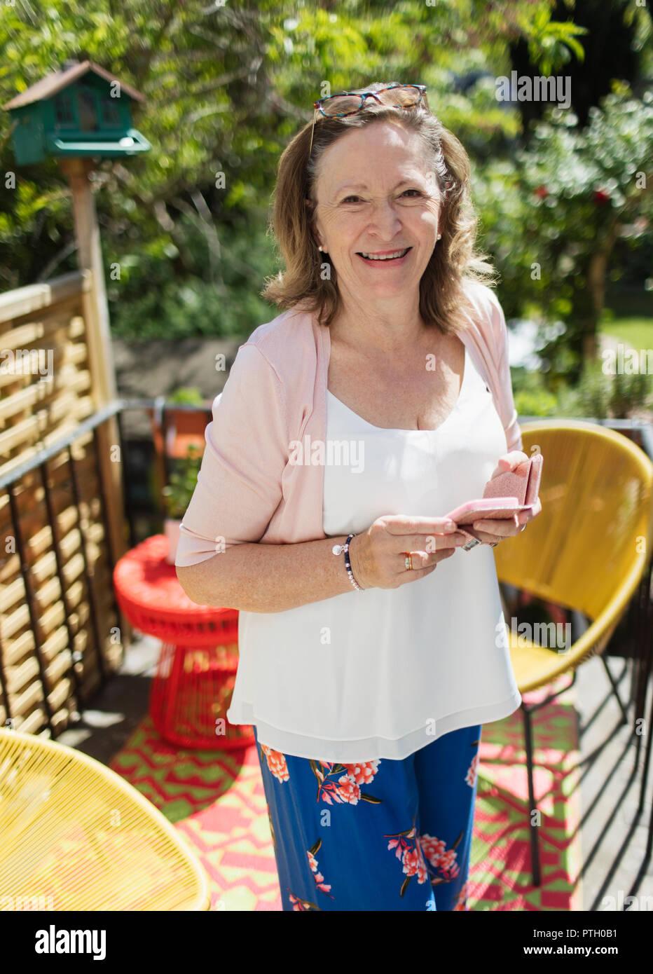 Portrait confident senior woman using smart phone on sunny patio - Stock Image