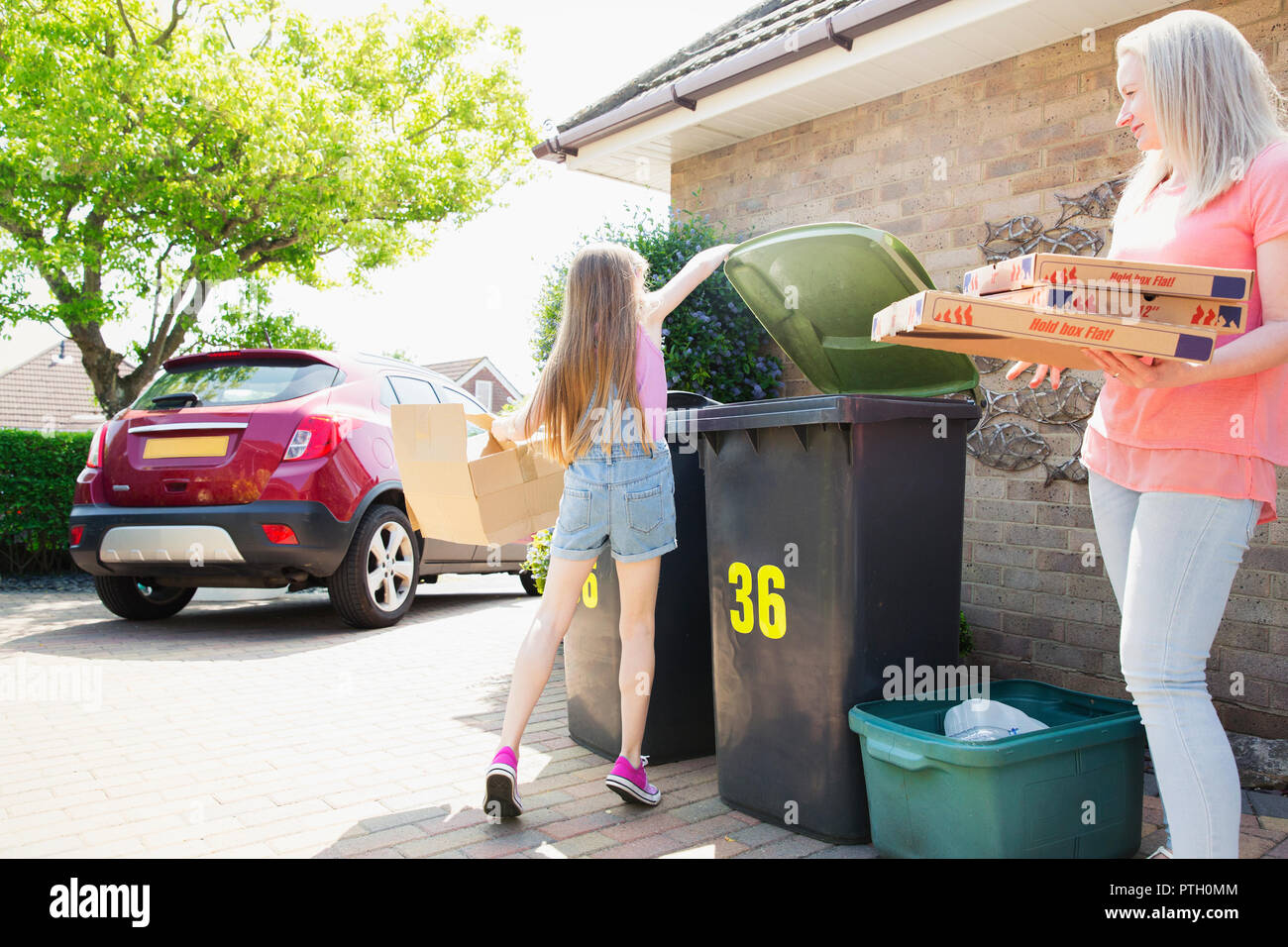 Mother and daughter recycling cardboard in driveway - Stock Image
