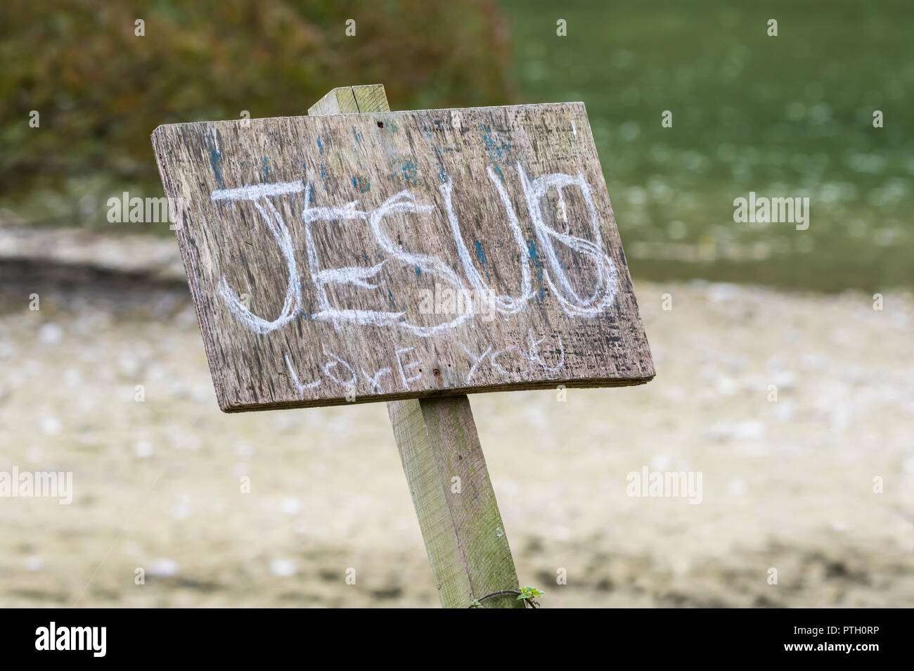 Sign outside with graffiti saying 'Jesus loves you', a religeous message to promote the Christian belief, in the UK. - Stock Image