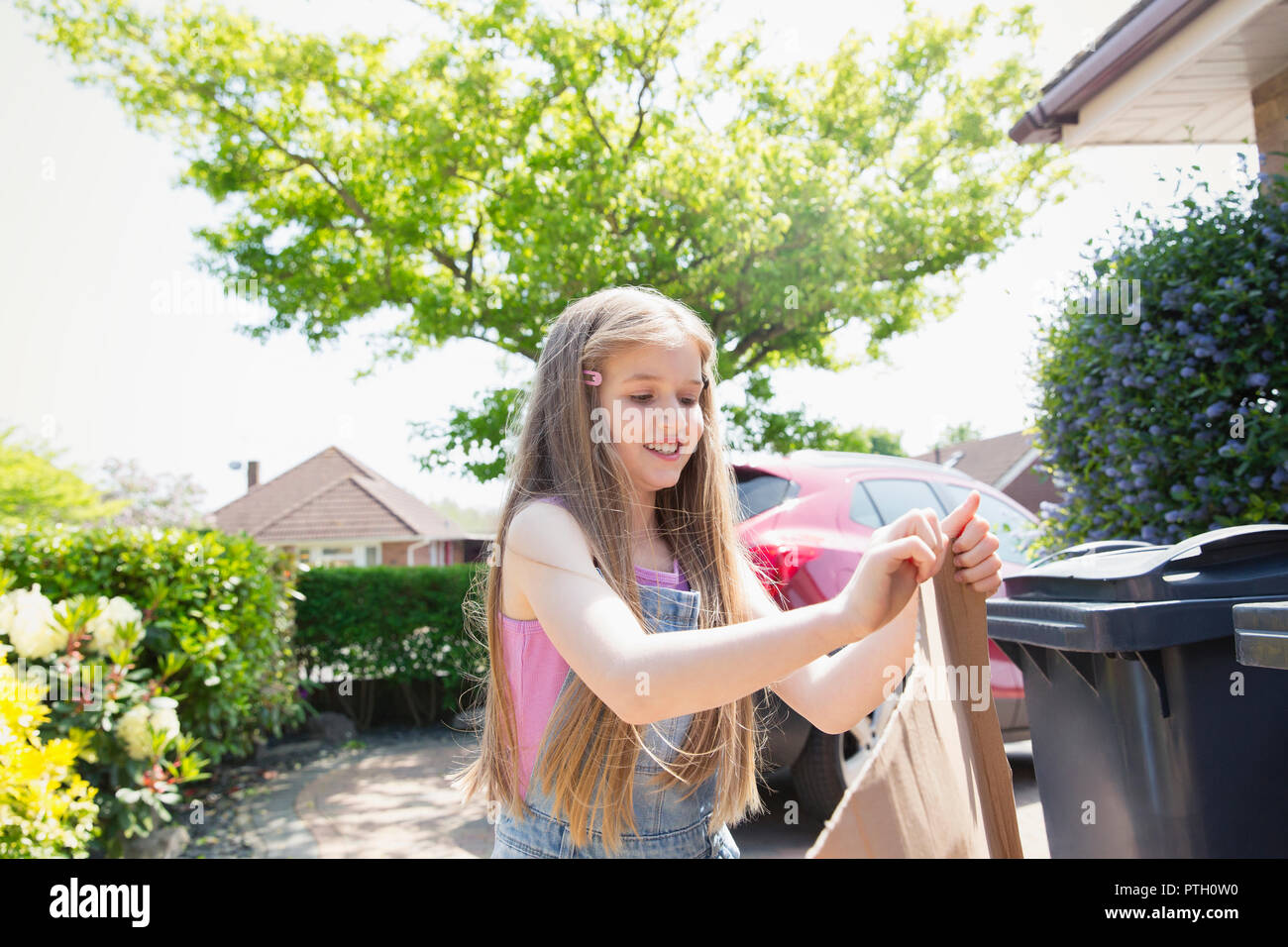 Girl recycling in sunny driveway - Stock Image