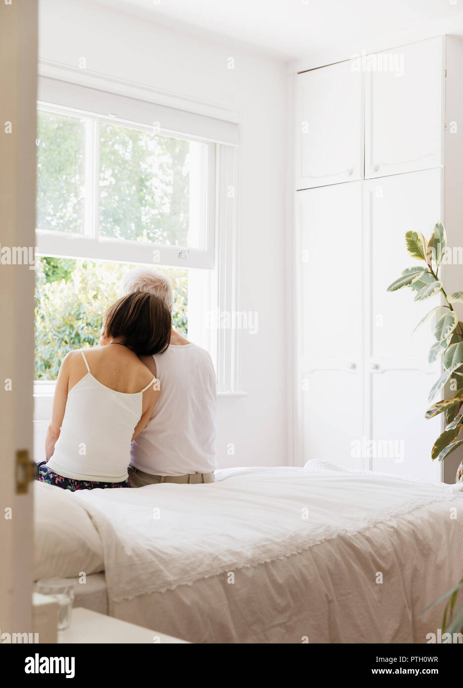 Serene senior couple sitting on bed and looking out window Stock Photo