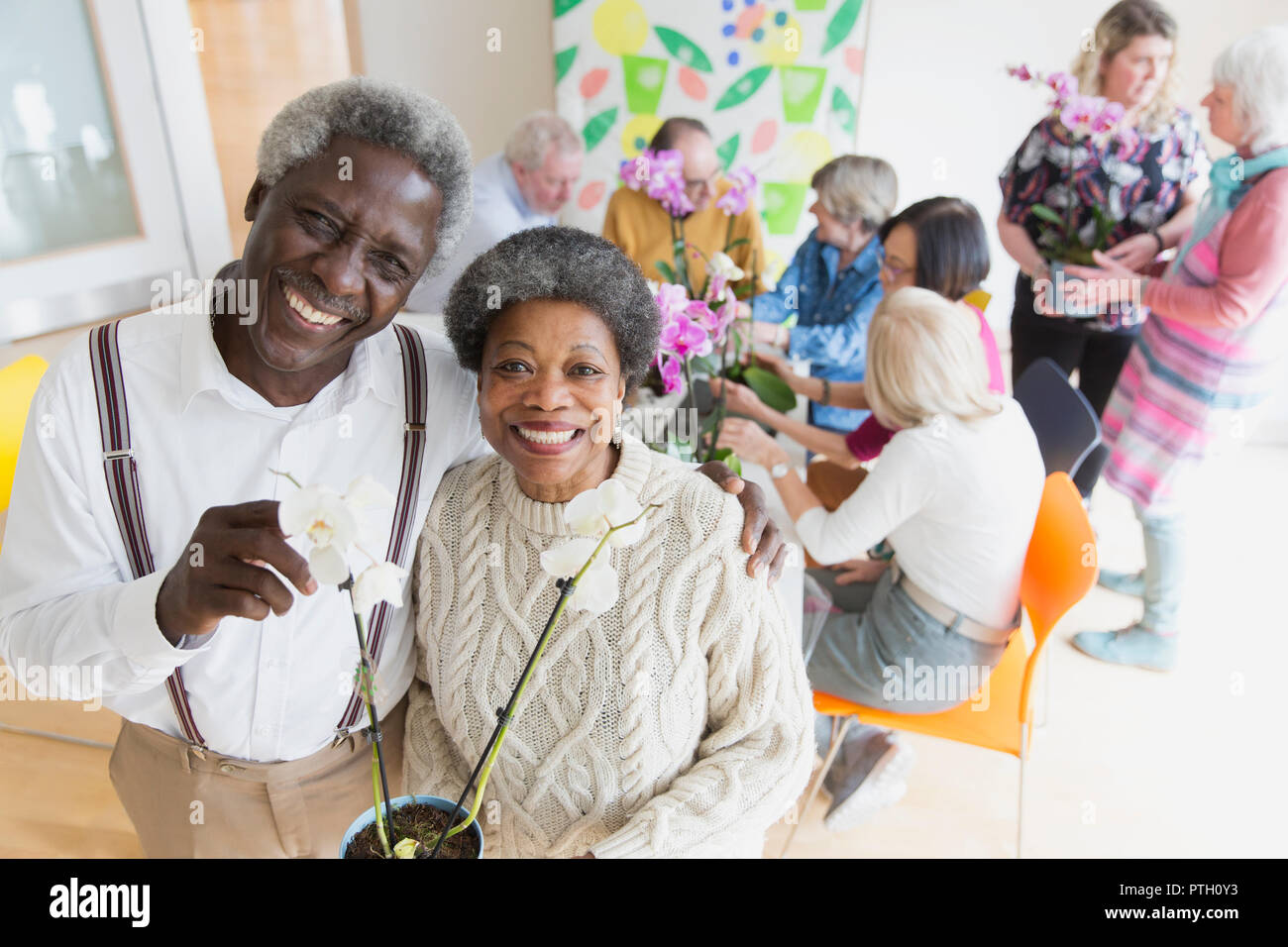 Portrait happy active senior couple enjoying flower arranging class - Stock Image