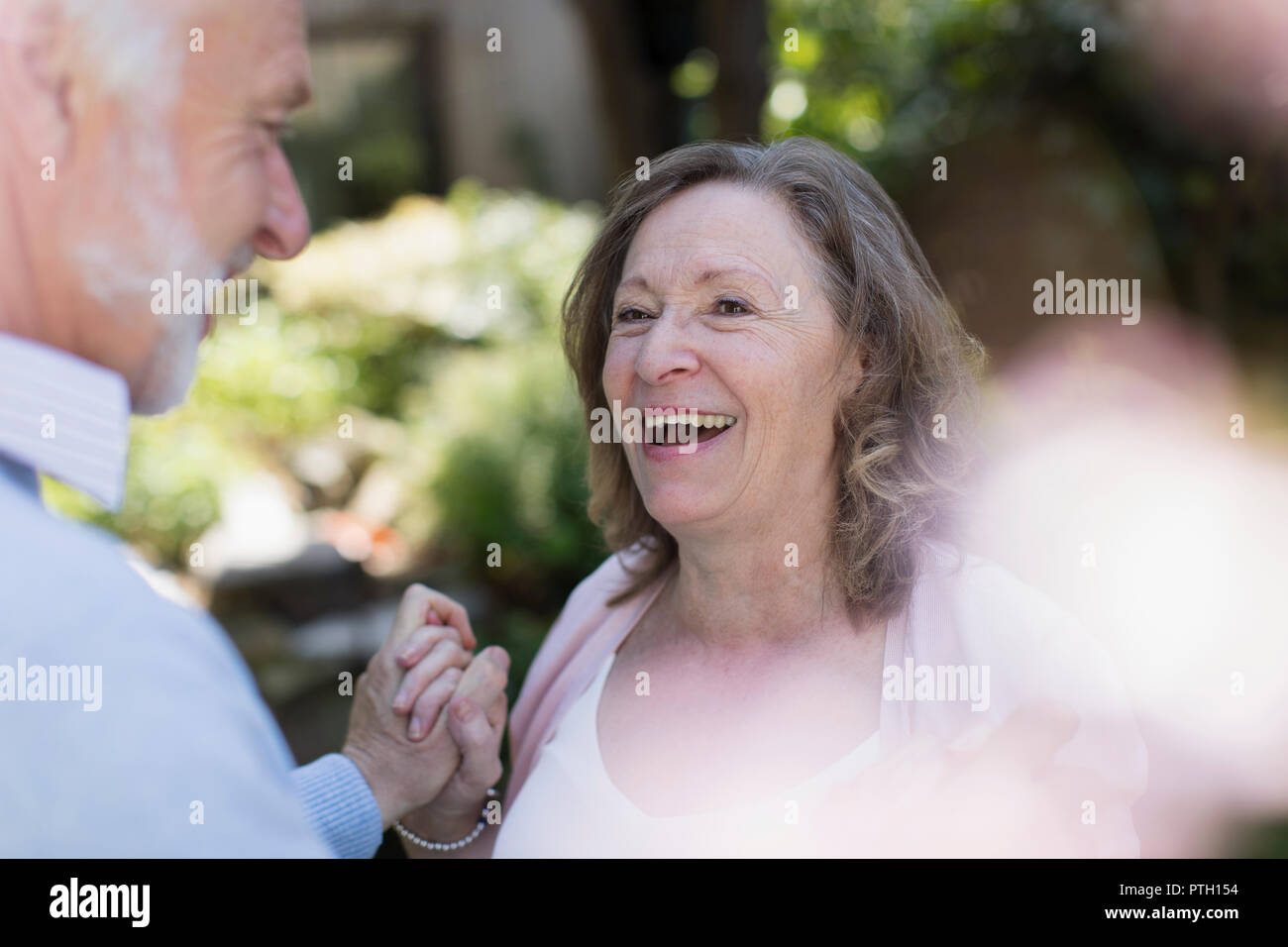 Happy, affectionate senior couple in garden - Stock Image