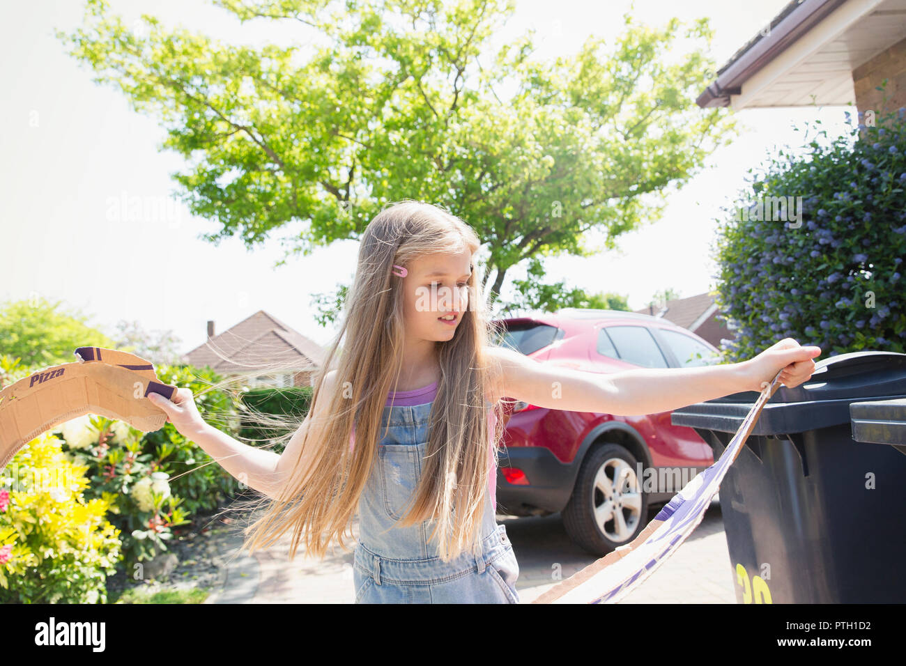 Girl recycling in driveway - Stock Image