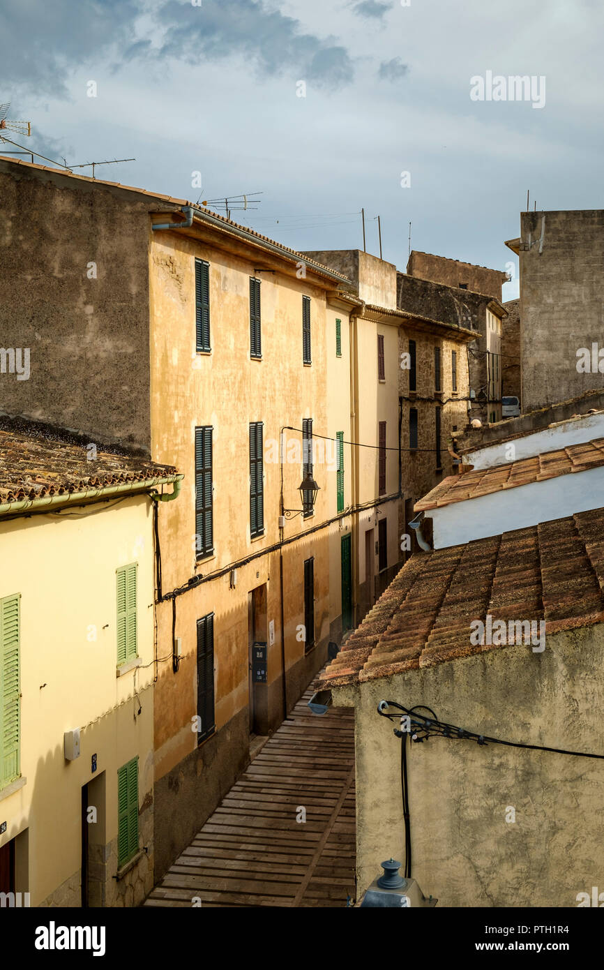 Typical buildings with traditional green shutters, terracotta roof tiles and ochre coloured stucco facade, the old town of Alcudia, Mallorca, Spain - Stock Image