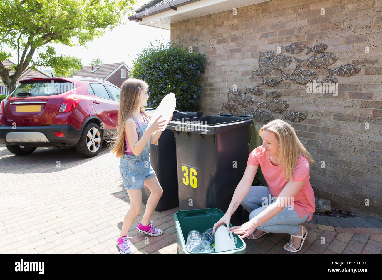 Mother and daughter recycling plastic outside house - Stock Image